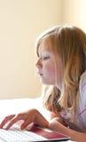 Rapariga que datilografa em seu portátil Imagem de Stock