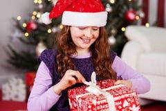 Rapariga que desempacota seu presente de Natal Imagem de Stock Royalty Free