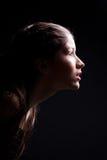 Rapariga que dura para a frente à luz no preto Imagem de Stock Royalty Free