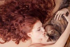 Rapariga que encontra-se com um gato Imagens de Stock Royalty Free