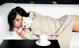 A rapariga que encontra-se em um sofá com o brinquedo do urso de peluche Fotos de Stock Royalty Free