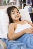 Rapariga que encontra-se na cama de hospital Fotos de Stock Royalty Free
