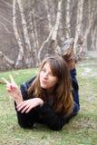 Rapariga que encontra-se na grama e nas mostras um sinal do peac Imagem de Stock Royalty Free