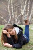 Rapariga que encontra-se na grama e no sorriso Fotos de Stock Royalty Free