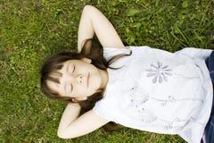 Rapariga que encontra-se para baixo na grama Imagem de Stock Royalty Free