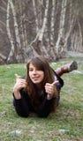 A rapariga que encontram-se na grama e as mostras entregam ESTÁ BEM o sinal Imagens de Stock Royalty Free