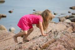 Rapariga que escala uma rocha Imagens de Stock