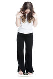 Rapariga que está nas escalas que medem o peso Imagem de Stock