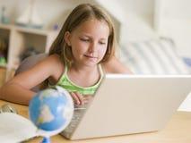 Rapariga que faz trabalhos de casa em um portátil Imagens de Stock Royalty Free