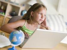 Rapariga que faz trabalhos de casa em um portátil Fotos de Stock