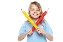 Rapariga que guardara lápis vermelhos e amarelos grandes Fotografia de Stock