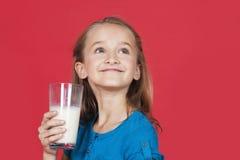 Rapariga que guardara o vidro do leite ao olhar acima no fundo vermelho Fotografia de Stock