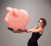 Rapariga que guardara um mealheiro enorme das economias Fotos de Stock Royalty Free