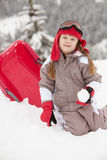 Rapariga que joga com o Sledge no feriado do esqui Fotos de Stock Royalty Free