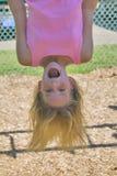 Rapariga que joga em barras de macaco no parque Foto de Stock Royalty Free