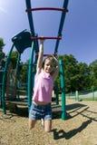 Rapariga que joga em barras de macaco no parque Fotografia de Stock