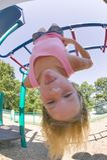 Rapariga que joga em barras de macaco no parque Imagens de Stock Royalty Free
