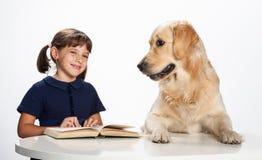 Rapariga que lê a seu cão fotografia de stock royalty free