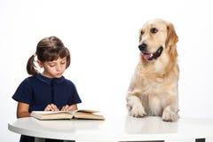 Rapariga que lê a seu cão foto de stock