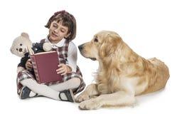 Rapariga que lê a seu cão imagem de stock royalty free