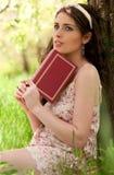 Rapariga que lê um livro sob a árvore de maçã Foto de Stock Royalty Free