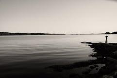 Rapariga que olha sobre a água calma Fotografia de Stock