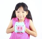Rapariga que prende o banco Piggy Foto de Stock Royalty Free
