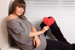 Rapariga que prende o coração nas mãos imagem de stock