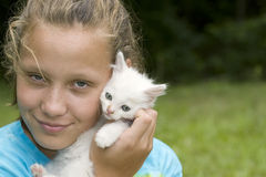 Rapariga que prende o gatinho branco Fotos de Stock Royalty Free
