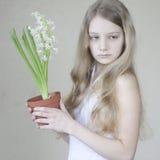 Rapariga que prende um potenciômetro das flores Foto de Stock