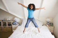 A rapariga que salta em sua cama Fotos de Stock Royalty Free