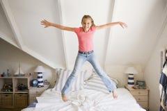 A rapariga que salta em sua cama Foto de Stock