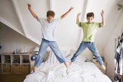 A rapariga que salta em sua cama Imagem de Stock Royalty Free