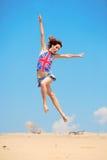 A rapariga que salta em um fundo do céu azul Imagem de Stock