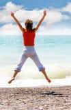A rapariga que salta na praia Fotos de Stock Royalty Free