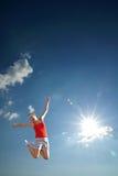 A rapariga que salta no céu imagens de stock royalty free