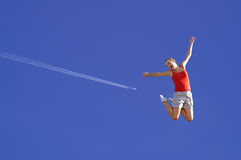 A rapariga que salta no céu imagens de stock