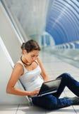 Rapariga que senta-se com um portátil Foto de Stock