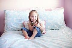 Rapariga que senta-se em sua cama Fotografia de Stock