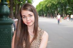 Rapariga que senta-se em um parque Imagens de Stock Royalty Free