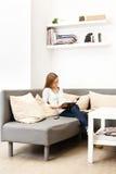 Rapariga que senta-se em um sofá em um quarto brilhante Imagens de Stock Royalty Free
