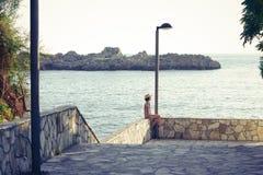 Rapariga que senta-se na frente do mar Imagens de Stock Royalty Free
