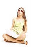 Rapariga que senta-se no assoalho usando um portátil fotos de stock royalty free