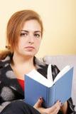 Rapariga que senta-se no sofá e que prende um livro foto de stock royalty free