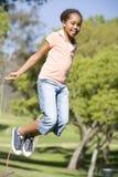 Rapariga que usa a corda de salto que sorri ao ar livre Fotos de Stock Royalty Free