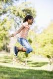 Rapariga que usa a corda de salto que sorri ao ar livre Imagem de Stock