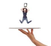 A rapariga salta mostrando o PC da tabuleta na mão dos povos Fotos de Stock