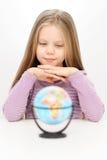 A rapariga segura bonita está olhando no globo do mundo Imagens de Stock