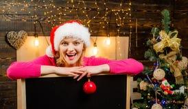 Rapariga sensual Mulher do Natal que guarda uma mesa preta para o texto Espaço preto da cópia da placa Forma do Natal seasonal imagens de stock