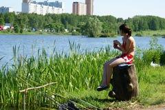 A rapariga senta-se na água e nos peixes Fotografia de Stock